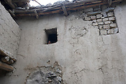 A young girl peers out of the window of her family home, Kargil District