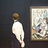 A Sotheby's employee passes in front of a painting entitled 'Vor Dem Ball (Zwei Frauen mit Katze)' by Max Beckmann (Est £5-8 million) during the press preview of the Sotheby's forthcoming February sales of Impressionist & Modern Art and Contemporary Art in London, including works by Picasso, Bacon, Monet, Richter, Miró, Basquiat.