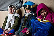 Moussa, 7, tries on a tourist's  ski helmet and goggles while Omina, 9, draws in a tourist's notebook.