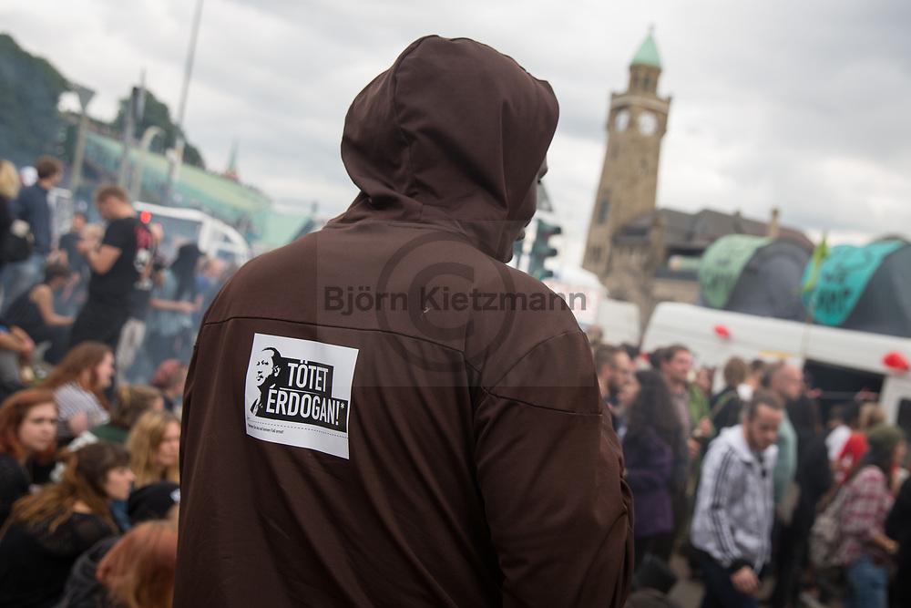 Hamburg, Germany - 05.07.2017<br /> <br /> &quot;Kill Erdogan&quot; sticker by the performance artists center for political beauty. Anti-G20 rave under the slogan &rdquo;Lieber tanz ich als G20&rdquo; (&quot;I prefer to dance instead of G20&rdquo;) goes through Hamburg. According to police, about 12,000 people are involved, according to the organizers more than 25,000 people participate.<br /> <br /> &quot;Toetet Erdogan&quot; sticker auf der Aktionskuenstler vom Zentrum fuer politische Schoenheit auf dem Ruecken eines Demonstranten. Anti-G20 Nachttanz-Demo unter dem Motto &rdquo;Lieber tanz ich als G20&rdquo; zieht durch Hamburg. Laut Polizei beteiligen sich etwa 12.000 Personen, laut den Veranstaltern nehmen mehr als 25.000 Menschen teil. <br /> <br /> Photo: Bjoern Kietzmann