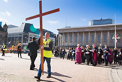 © Licensed to London News Pictures. 25/3/2016. Birmingham, UK. Good Friday Walk of Witness. Churches in Birmingham come together to walk through Birmingham City Centre, visiting Cathedrals and Churches. Pictured, the cross is carried through Victoria Square. Photo credit : Dave Warren/LNP