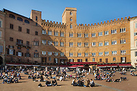 SIENA, ITALY - 20 MARCH 2015: People sit in Piazza del Campo, the principal square of Siena's historical center, in front of Palazzo Sansedoni, the headquarters of the Monte dei Paschi di Siena Foundation, in Siena, Italy, on March 20th 2015.<br /> <br /> The charitable Monte dei Paschi di Siena Foundation is the bank's largest shareholder that has financed projects in the fields of economic development, art and research. Until 2014, the Foundation has entirely funded Siena Biotech, a clinical-stage drug discovery company whose  efforts are mainly focused on discovering new drugs for therapeutic intervention against neurodegenerative diseases and in oncology, such as Alzheimer&rsquo;s Disease, Huntington&rsquo;s Disease and Cancer.<br /> <br /> Now Siena Biotech has filed for bankruptcy proceedings, and its researchers and employees occupied the headquarters of the company based in Siena.<br /> <br /> Siena, a Tuscan city and UNESCO World Heritage Site, is home to Monte dei Paschi di Siena, the world's oldest surviving bank and Italy's third largest bank. The bank, founded in 1472, was the largest employer in Siena, and it helped finance a host of community projects and services until it stumbled during the financial crisis started in 2008.
