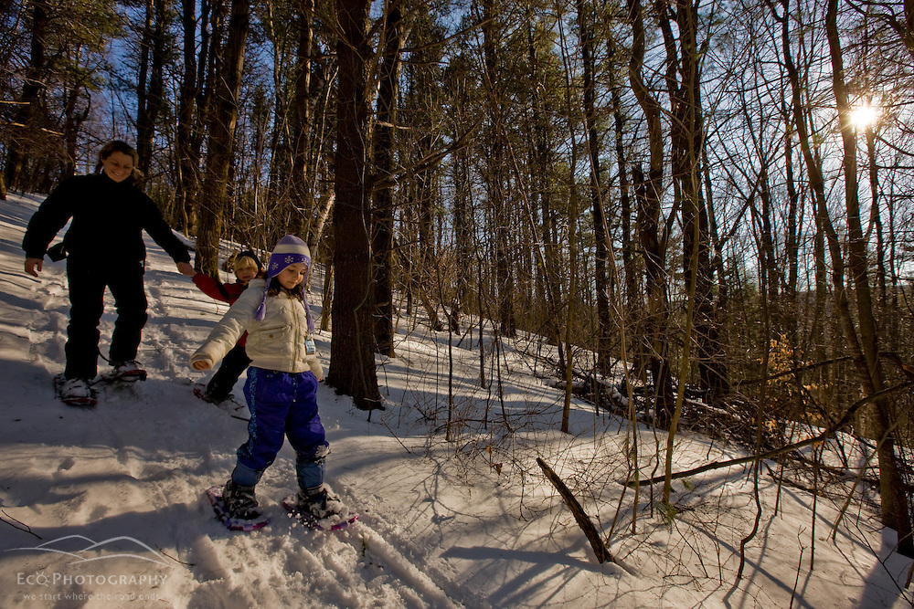 A woman and her two kids snowshoe through the woods  at the Tyringham Cobble Reservation in Tyringham, Massachusetts.  Berkshire Mountains. The Trustees of Reservations.