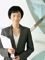 Smiling businesswoman standing holding clipboard