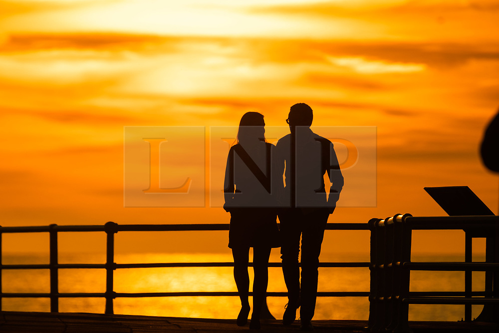 ©Licensed to London News Pictures. 18/09/2019 Aberystwyth UK. The sun setting gloriously over  Cardigan Bay silhouettes people walking along the promenade at the end of a day of unbroken clear blue skies and warm September sunshine in Aberystwyth ,  as the 'indian summer' mini heat-wave continues over much of the souther parts of the UK. Photo credit Keith Morris/LNP