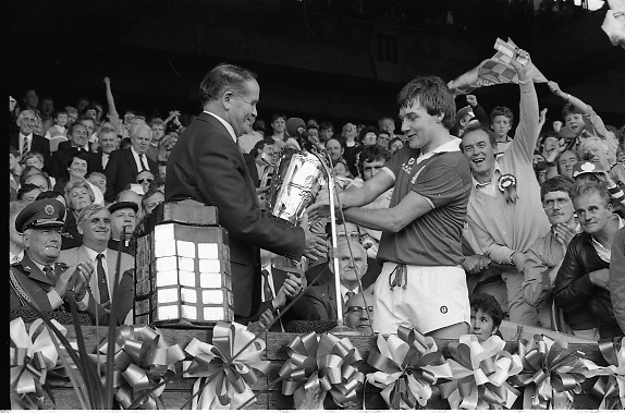 All Ireland Hurling Finals.1986..07.09.1986..09.07.1986..7th September 1986..September,every year,is the highlight of the GAA calendar with The All Ireland Finals being held in both codes. The senior and minor finals in each code are both played for on the same day. Each finalist has battled through provinical and knock out stages to reach the final.It is widely regarded as the pinnacle of a players career to reach and win an All Ireland Championship..In this years hurling finals,Cork played Offaly in the minor championship and a much fancied Galway team took on Cork in the senior final. Both matches were well fought and close encounters...Photo of the winning captain,Corks' Tom Cashman, as he is presented with the Liam McCarthy Cup by Dr Michael Loftus,President of the GAA.