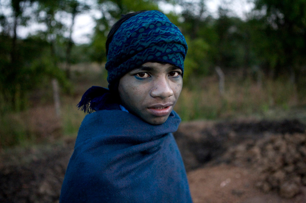 A dye factory worker on their way to work in the morning. Even after bathing the dye stain remains on their skin.