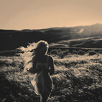 Woman with long blonde hair walking alone outdoors in large rural landscape with low sunlight