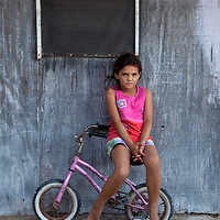 Young Belizean Girl Sitting on Small Bicycle in San Pedro, Belize