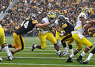 November 05, 2011: Iowa Hawkeyes linebacker James Morris (44) tries to pull down Michigan Wolverines running back Fitzgerald Toussaint (28) during the first quarter of the NCAA football game between the Michigan Wolverines and the Iowa Hawkeyes at Kinnick Stadium in Iowa City, Iowa on Saturday, November 5, 2011. Iowa defeated Michigan 24-16.