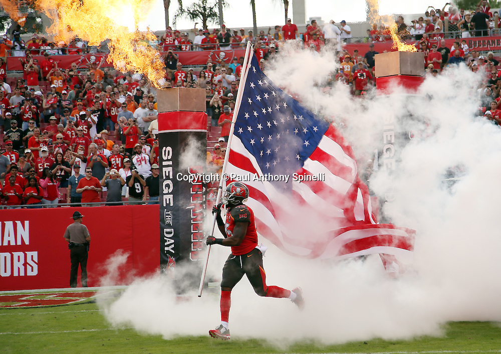 Tampa Bay Buccaneers linebacker Orie Lemon (45) runs out of a cloud of white smoke and onto the field carrying a large American flag before the 2015 week 14 regular season NFL football game against the New Orleans Saints on Sunday, Dec. 13, 2015 in Tampa, Fla. The Saints won the game 24-17. (©Paul Anthony Spinelli)