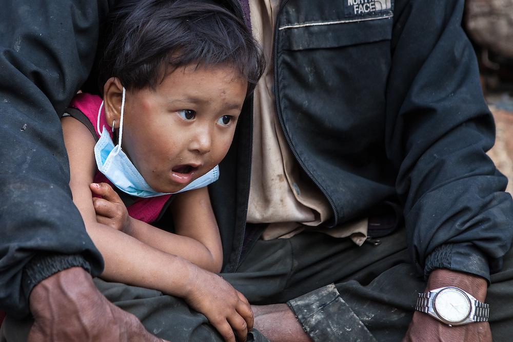 Meisje met gezichtsmasker in de armen van haar vader in de grotendeels verwoeste stad Sakhu, nabij Kathmandu.