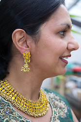 Profile of woman wearing traditional Asian dress and jewellery smiling,
