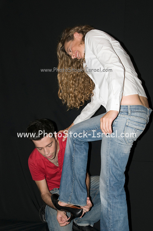 A young couple in their 20s man helping woman put on a shoe on a black background Model Releases available