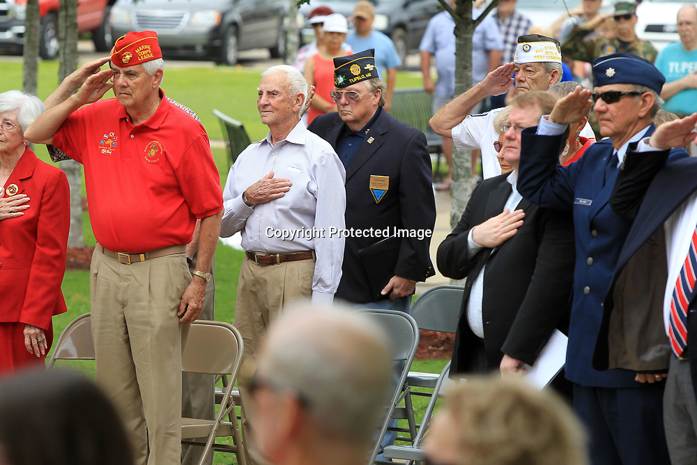 United States Armed Forces Veterans stand at attention and salute during the playing of taps by MGySgt Bob Verell, US Marine Corps Retired, at the conclusion of Tupelo's Memorial Day Service held at Veterans Park Monday morning.