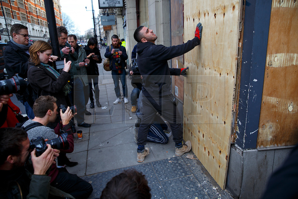 © Licensed to London News Pictures. 25/01/2016. London, UK. Workers covering a new Banksy mural with a wooden board, the artwork criticising the use of teargas on refugees in Calais has appeared on a building opposite the French Embassy in London on Monday, 25 January 2016. The artwork was uncovered only minutes after it was covered by the workers of the building that it appeared on. Photo credit: Tolga Akmen/LNP