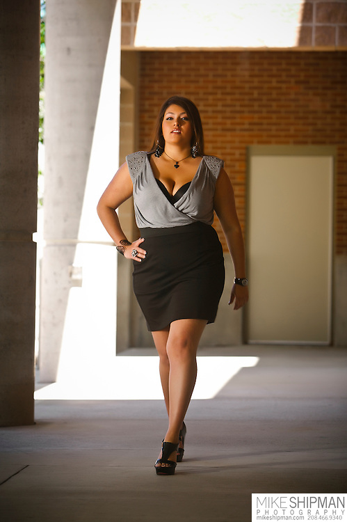 Plus size model wearing black skirt and black and white top walking toward camera