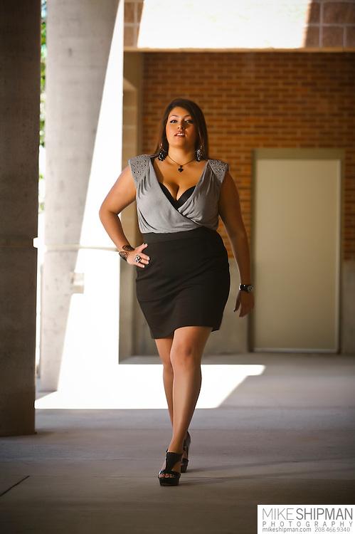 Plus size model wearing black skirt and black and white top walking toward camera
