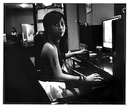 Young tattooed girl spends evening accessing a chatroom at a internet café at night, Shantou, China.