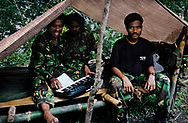 Falintil guerrillas relaxing at their base camp. <br />