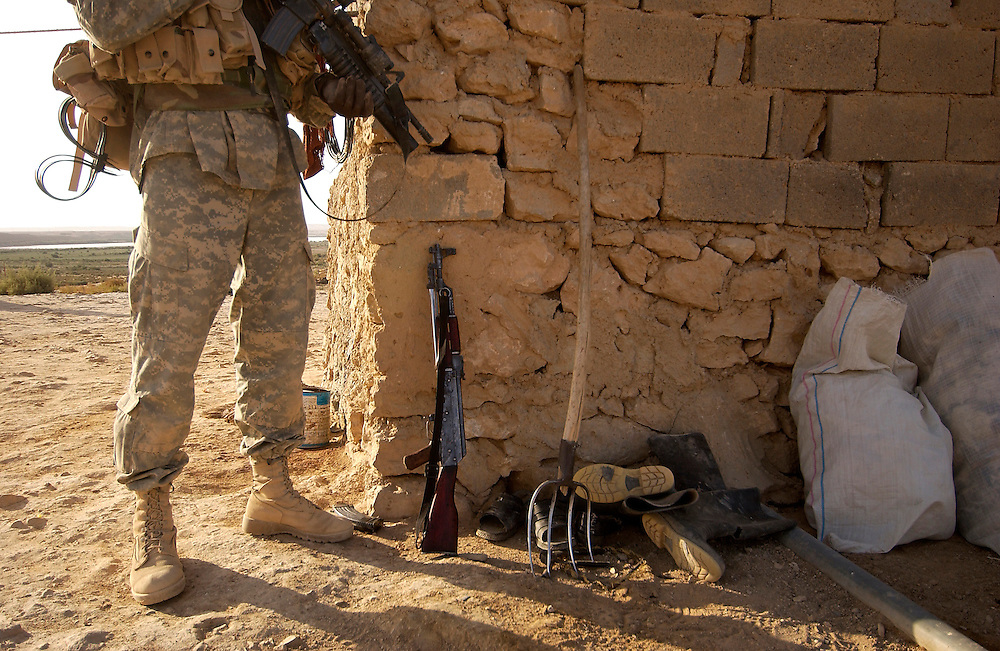 Soldiers find an AK-47 in a Iraqi mans house.