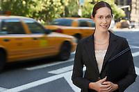 Businesswoman holding portfolio in street portrait