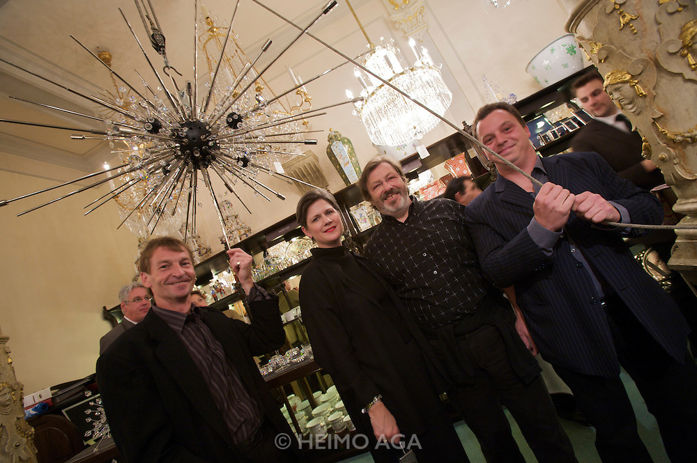 """Lobmeyr employees and Elizabeth (""""Liz"""") Hurley (Director of Development, Metropolitan Opera) with a partly renovated Chandelier during a reception at Lobmeyr/Vienna to celebrate the restauration of 11 crystal chandeliers Lobmeyr had created for the foyer and auditorium of New York's Metropolitan Opera, in 1966..The Sputnik-like steel structures with 51.000 individual crystals are completely dismantled, cleaned, and re-built from the ground, while many missing crystals and damaged or outdated parts are being replaced. This takes approximatley one month..Lobmeyr's prestigeuos client list includes H.R.H. Queen Elisabeth II., the Sultan of Brunei, Arnold Schwarzenegger and many others."""