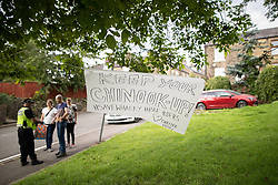 "© Licensed to London News Pictures. 04/08/2019. Whaley Bridge, UK. Poster reading "" Keep your chinook up "" as residents (pictured in the background) bring food and drinks for emergency service workers . Residents just outside the cordon erect signs thanking emergency services . Further homes have been evacuated overnight and more rain is forecast today (Sunday 4th August) in the town of Whaley Bridge in Derbyshire after earlier heavy rain caused damage to the Toddbrook Reservoir , threatening homes and businesses with flooding. Photo credit: Joel Goodman/LNP"
