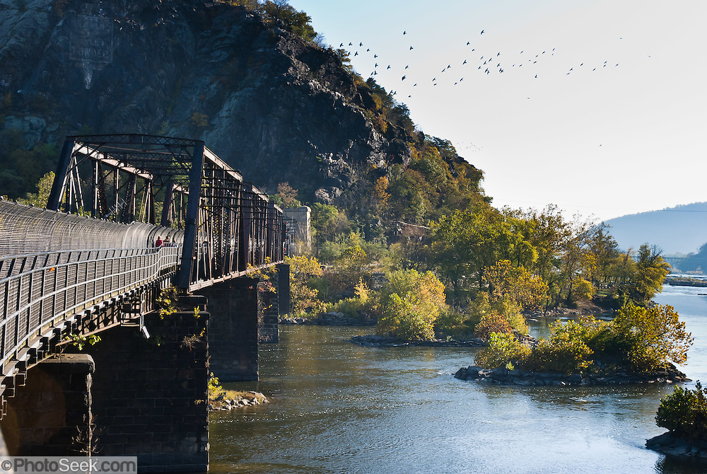 The Baltimore and Ohio Railroad Crossings at the Potomac River are a set of railroad bridges (on the National Register of Historic Places) that span the Potomac River between Maryland Heights, Maryland and Harpers Ferry, West Virginia, USA. Two bridges comprise the current crossing. in this image is the older bridge, a steel Pratt truss and plate girder bridge dating to 1894, carrying the B&O Valley line toward Winchester, Virginia along the Shenandoah River. A tunnel was built at the same time as the 1894 bridge to carry the tracks through Maryland Heights and to eliminate a sharp curve. The western end of the tunnel was widened in conjunction with the construction of the second bridge to allow the broadest possible curve across the river. Just downstream of the 1894 bridge, almost at the confluence of the Potomac and Shenandoah Rivers, are the ruins of two previous bridges on the same alignment. The newer of the bridges was a Bollman truss bridge that carried rail and highway traffic from 1870 until 1936, when it was swept away by a flood. As of 2008, Amtrak, the US national passenger rail system, provides service to Harpers Ferry twice a day (once in each direction). It is also served by the MARC commuter rail service, on its Brunswick line. The city's passenger rail station is located at the West Virginia end of the historic railroad bridge across the Potomac River. In addition about forty or fifty CSX freight trains daily pass through Harpers Ferry and over the bridge spanning the Potomac River.