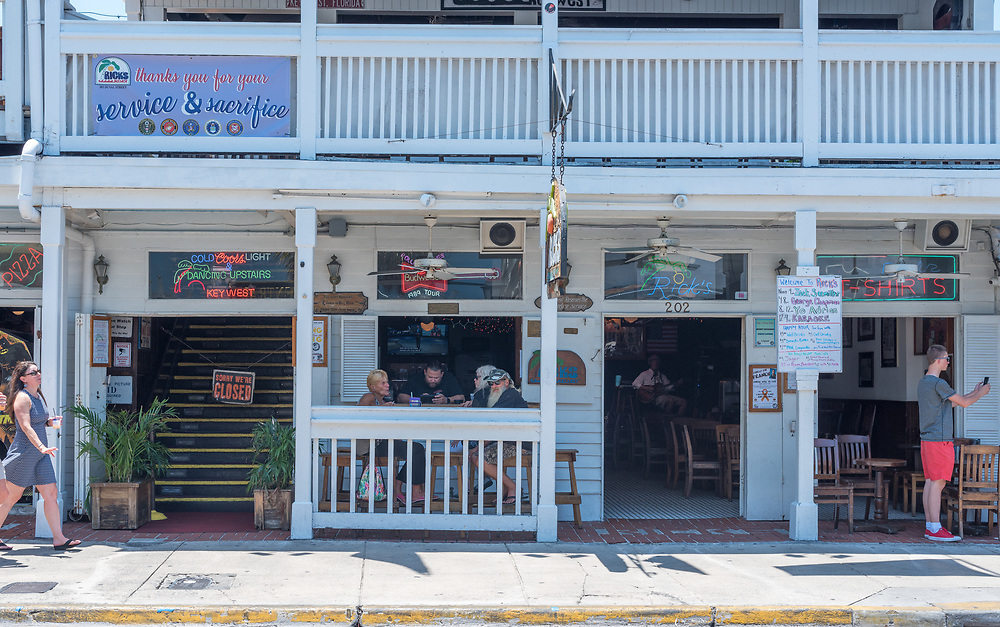 Key West, Florida--April 29, 2018.  Patons relax in Rick's Bar in Key West as pedestrian approaches and another snaps a photo with a mobile phone. Editorial Use Only.