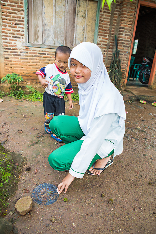 CAPTION: Dwi has been eager to put in to practice what she has learned about climate change. Here, she points out one of the biopores she's recently installed at the front of her house. LOCATION: Dwi Wijayanti's house, Jl. St. Badaruddin II No 56, Bandar Lampung, Indonesia. INDIVIDUAL(S) PHOTOGRAPHED: Dwi Wijayanti and her younger brother Muhammad.