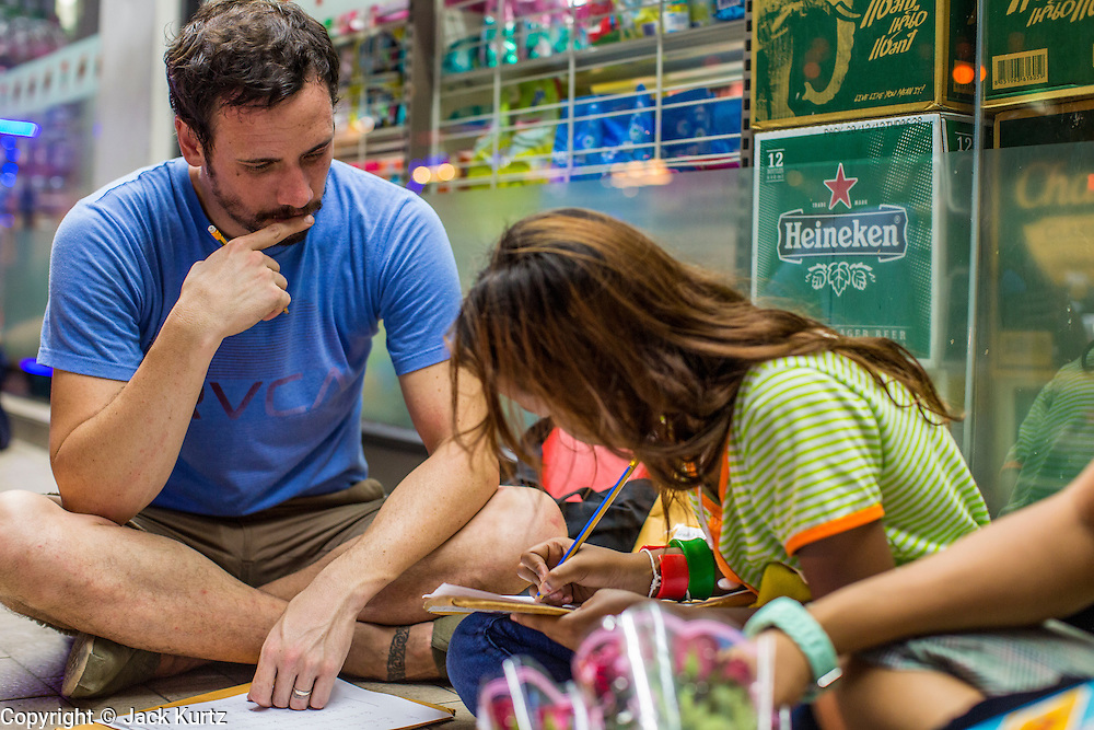 01 APRIL 2013 - BANGKOK, THAILAND:  Tim Hupe leads a math class for Cambodian children who work on the streets of the Nana red light district in Bangkok. The children The beg from tourists and also sell them roses and flowers.  PHOTO BY JACK KURTZ