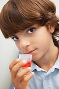 Boy holding medicine in liquid measure,portrait