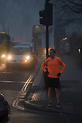 A jogger waits to cross in front of commuter traffic at dawn on a foggy morning in south London.