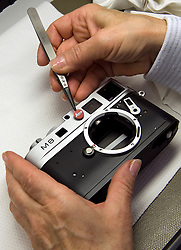 SOLMS, GERMANY - MAY-18-2009 - Technicians apply the finishing touches to a Leica M8 digital camera. (Photo © Jock Fistick)