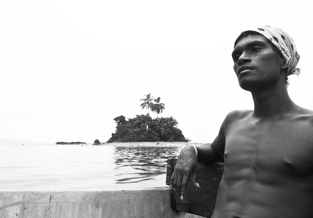 A man looks pensive with a small tropical island in the background