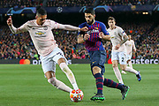 Manchester United Defender Chris Smalling tackles Barcelona forward Luis Suarez (9) during the Champions League quarter-final leg 2 of 2 match between Barcelona and Manchester United at Camp Nou, Barcelona, Spain on 16 April 2019.