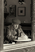 Man photographed through a window hunched over his beer in contemplation.