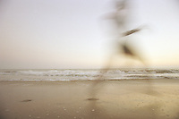 Woman running on beach (blurred motion)