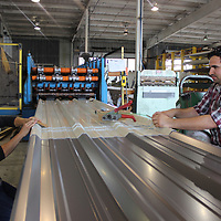 Chris Gilmore, left, and Evan Bullock work on a sheet of metal.