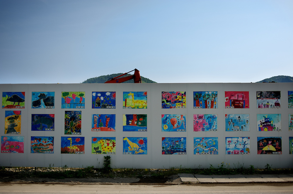 May 27, 2013 - Ishinomaki, Japan: Construction goes ahead, in a area affected by the 2011 tsunami that hit the east coast of japan, behind a protective wall ornate with pictures painted by children of a local school. (Paulo Nunes dos Santos)
