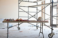 Table with blueprints and hardhat in front of scaffold in construction room