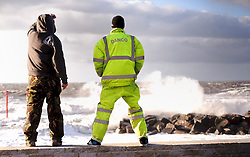 St Judes storm lashes at the South of England.<br /> St Judes storm batters the South of Two workers battle the breakwater after the storm, West Bay, Devon, UK.  Monday, 28th October 2013. Picture by i-Images