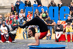 Edinburgh, Scotland, UK. 15 August 2019. Warm sunny weather in Edinburgh brought thousands of tourists onto the Royal Mile to enjoy the many street performers and actors promoting their shows during the Edinburgh Festival Fringe. Contortionist No Bones Jones from Australia performs. Iain Masterton/Alamy Live News ++ Editorial Use Only ++