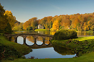 A autumn view of the bridge, lake and temple at Stourhead Landscape Garden; Stourton, Wiltshire, Uk