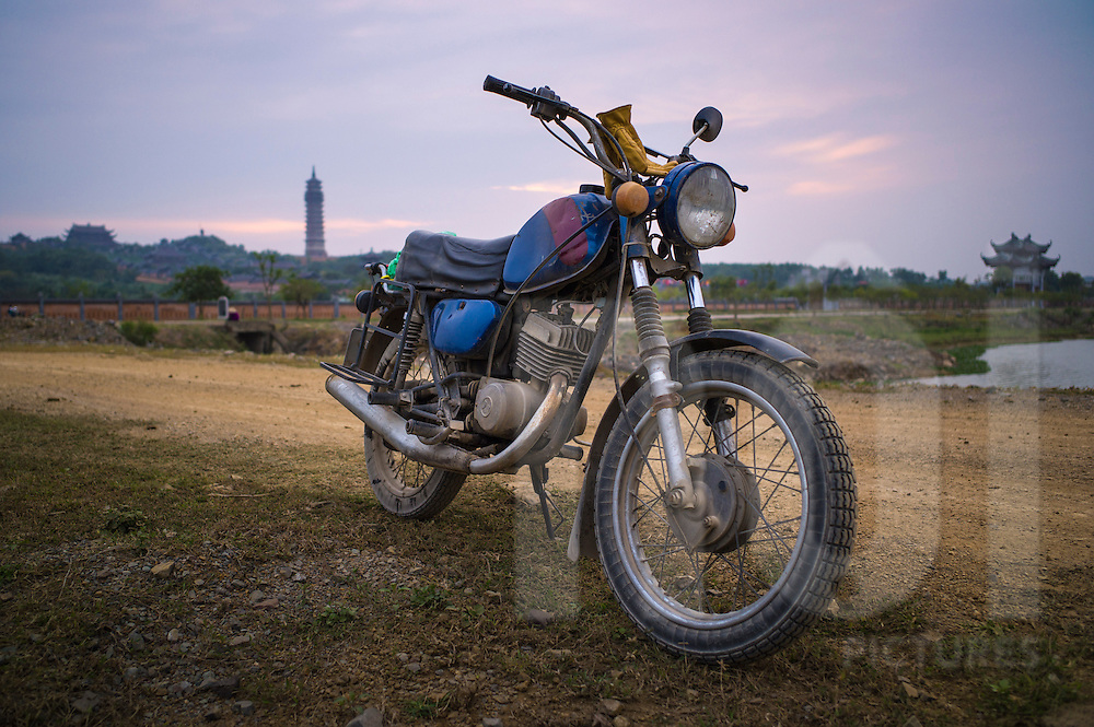 Deserted Minsk motorbike parked on the side of a dirt road outside of Bai Dinh Pagoda complex, Ninh Binh Province, Vietnam, Southeast Asia