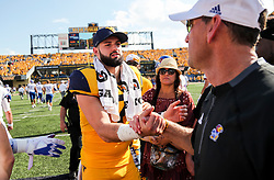 Oct 6, 2018; Morgantown, WV, USA; West Virginia Mountaineers quarterback Will Grier (7) talks with Kansas Jayhawks head coach David Beaty after the game at Mountaineer Field at Milan Puskar Stadium. Mandatory Credit: Ben Queen-USA TODAY Sports
