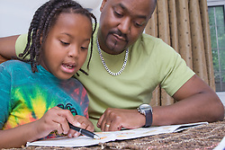 Father helping his young daughter with her homework,