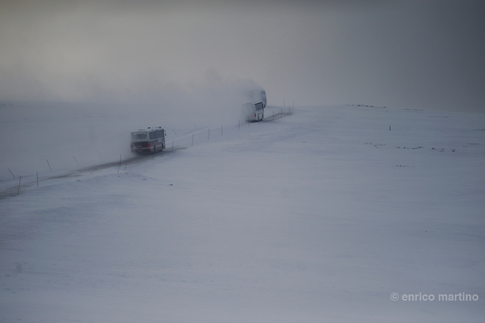 Bus convoy on winter on North Cape road. North Cape is a cape on the island of Magerøya in northern Norway, in the municipality of Nordkapp. Its 307 m high, steep cliff is often referred to as the northernmost point of Europe, located at 71°10?21?N, 2102.3 km from the North Pole.
