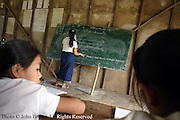 Ban Buamlao Primary School teacher Nang Chanton writes notes on the board as student study.  Lacking basic learning utensils, many students find the early years of their public school education in Laos the most difficult according to the faculty members.